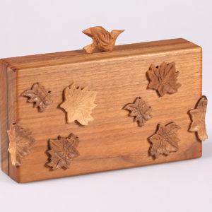 Clutch in noce con decori intagliati in legno massello, finitura opaca
